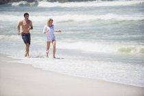 Счастливая пара, бегающая вместе по песчаному пляжу — стоковое фото