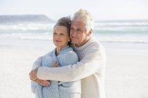 Счастливый мужчина с женой сзади на пляже — стоковое фото
