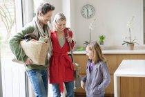 Счастливая семья входит в дом и улыбается — стоковое фото