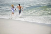 Rear view of cheerful couple running in water on beach — Stock Photo