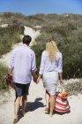 Vue arrière du couple marchant sur la plage en tenant la main avec sac et parasol — Photo de stock