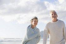 Счастливая старшая пара, гуляющая по пляжу под облачным небом — стоковое фото