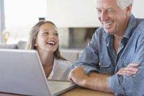 Mann zeigt Enkelin Laptop und lacht — Stockfoto