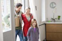 Familia feliz entrando en casa y sonriendo - foto de stock