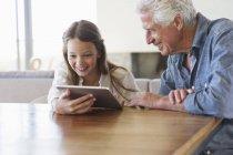 Chica usando tableta digital con el abuelo sentado en el escritorio - foto de stock