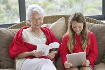 Senior woman reading book with granddaughter using digital tablet — Stock Photo