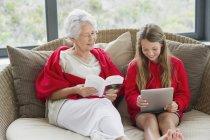 Donna anziana che legge libro con nipote utilizzando tablet digitale — Foto stock