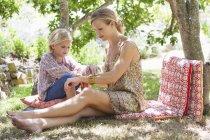 Mãe e menina sentados no quintal no verão — Fotografia de Stock