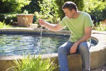 Mature man sitting at poolside in garden and touching water — Stock Photo