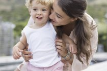 Крупный план счастливой матери, играющей с сыном на открытом воздухе — стоковое фото