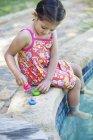 Маленькая девочка играет с резиновыми утками на краю бассейна — стоковое фото