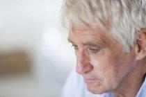 Крупный план задумчивого пожилого человека, смотрящего вниз — стоковое фото