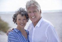 Счастливая пожилая пара стоит на пляже и смотрит в камеру — стоковое фото