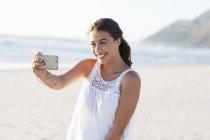Glückliche junge Frau nehmen Selfie mit Smartphone am Strand — Stockfoto