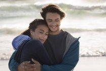 Счастливая романтическая молодая пара, обнимающаяся на пляже — стоковое фото