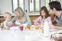Happy family having fun at breakfast table — Stockfoto