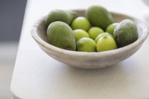 Close-up of lemons and avocados in bowl on white table — Stock Photo