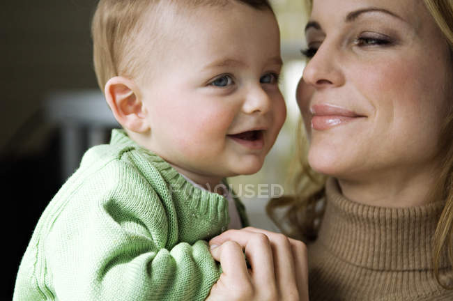 Портрет улыбающейся матери с маленьким мальчиком на руках — стоковое фото