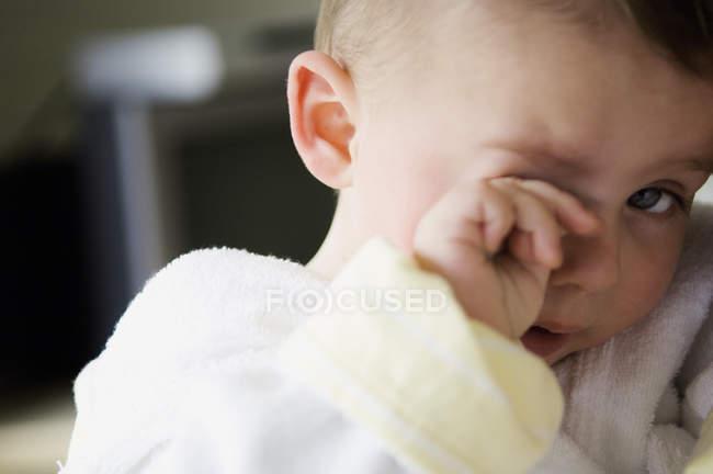 Retrato de bebé cansado frotando el ojo - foto de stock
