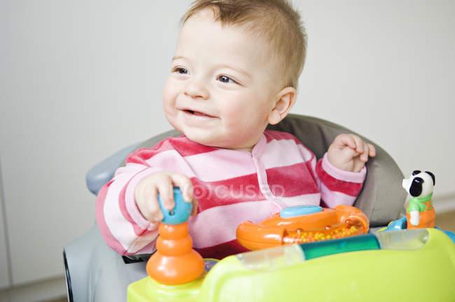 Cheerful baby boy sitting in baby-walker and looking away — Fotografia de Stock