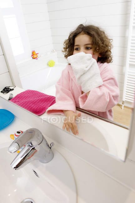 Little girl wiping face with towel in bathroom — Stock Photo