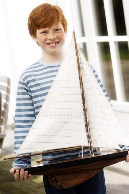 Ruiva menino segurando modelo de barco e olhando para a câmera — Fotografia de Stock