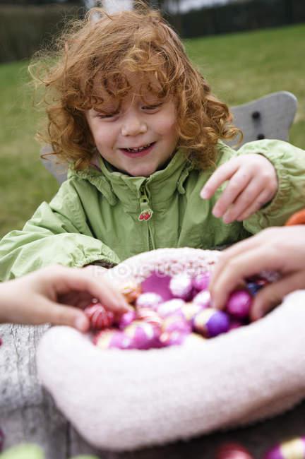 Дівчинка імбиру грати з великодні яйця на відкритому повітрі — стокове фото