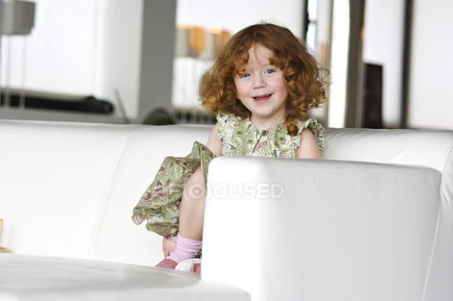 Portrait of little ginger girl sitting on a sofa — Stock Photo