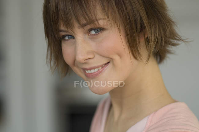 Portrait of smiling woman with short hair looking at camera — Stock Photo