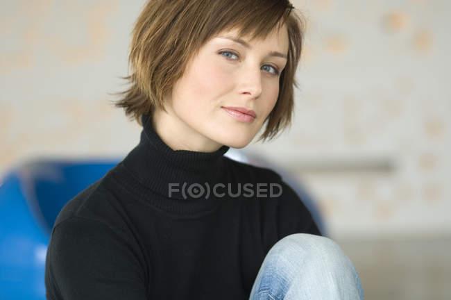 Ritratto di donna con i capelli corti seduta e guardando la macchina fotografica — Foto stock