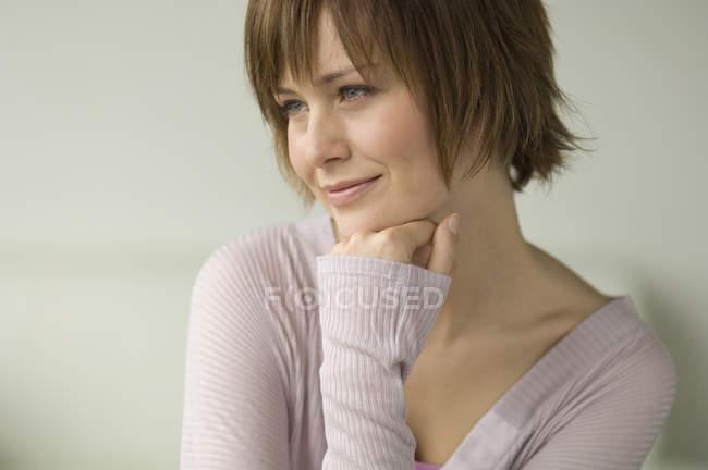 Портрет улыбающейся женщины с короткими волосами, смотрящей в сторону — стоковое фото