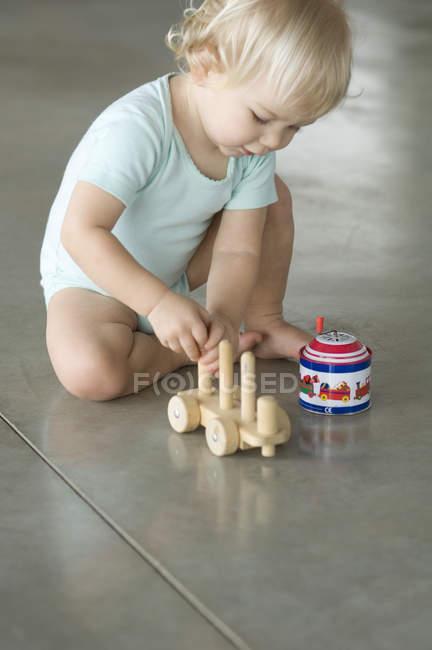 Kleiner blonder Junge spielt auf dem Fußboden mit Spielzeug — Stockfoto