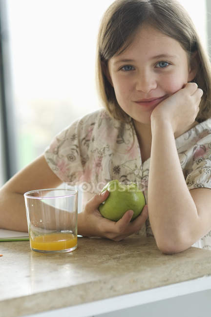 Portrait of smiling little girl eating apple at table — Stock Photo