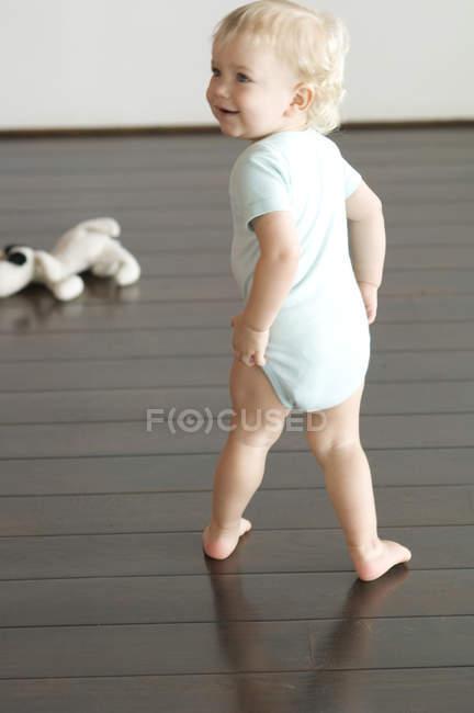 Усміхнений маленький хлопчик ходить на дерев'яну підлогу і дивиться — стокове фото