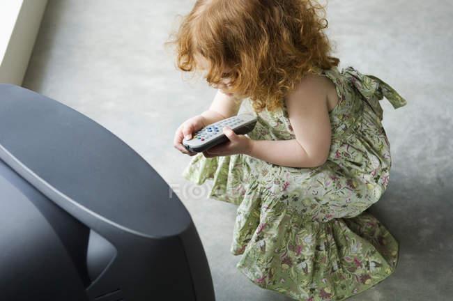 Petite fille de gingembre accroupie devant la télévision, retenant la télécommande — Photo de stock