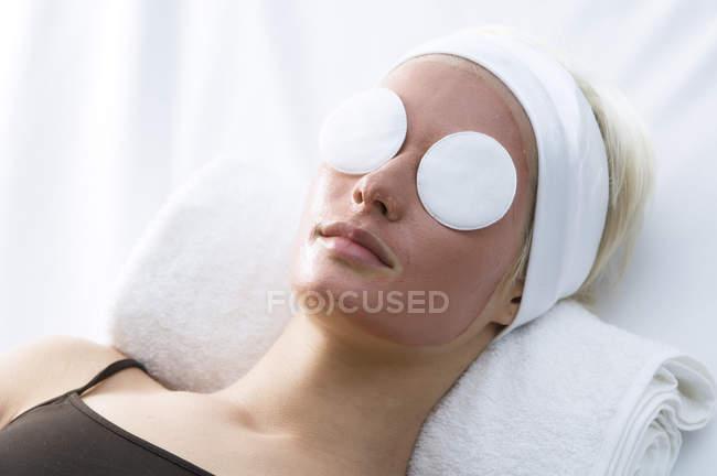 Портрет молодой женщины в маске красоты на лице и очищающих хлопковых подушечках на глазах — стоковое фото