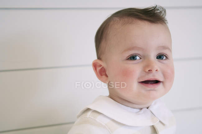 Portrait of cute baby boy smiling against wall — Stock Photo