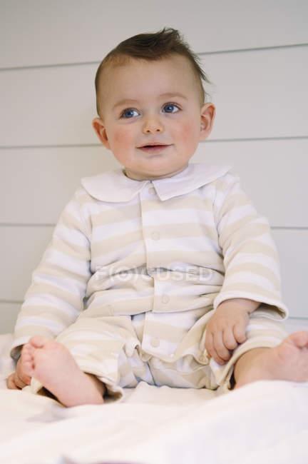 Милый мальчик улыбается, сидя на кровати — стоковое фото