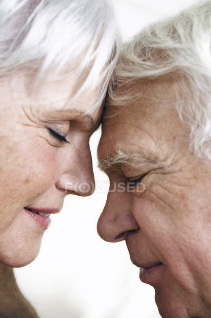 Close-up of senior couple face to face with eyes closed — Stock Photo