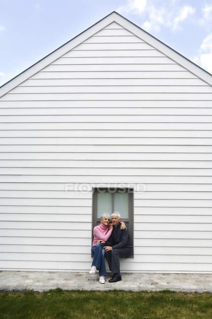 Senior couple embracing, sitting on window sill of white house — Stock Photo