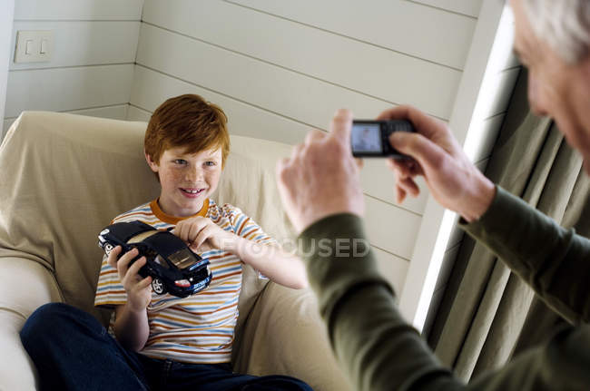 Senior man taking picture of boy with camera phone — Stock Photo