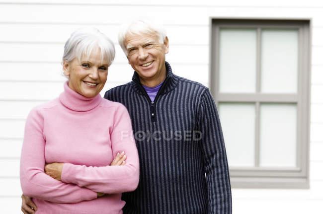 Ritratto di sorridere coppie senior che stanno davanti casa — Foto stock
