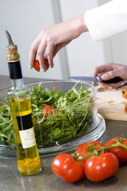 Mains féminines faisant de la salade dans la cuisine, gros plan — Photo de stock