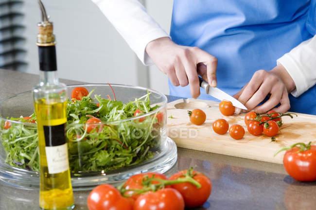Woman making salad, chopping tomatoes, selective focus — стокове фото