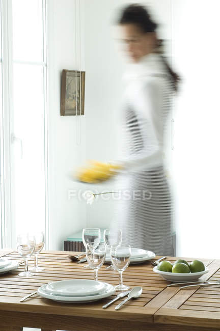Wooden setting table and blurred woman on background — Stock Photo