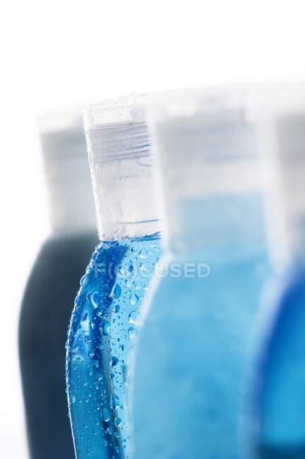 Close-up de botellas azules de agua cae sobre el fondo blanco - foto de stock