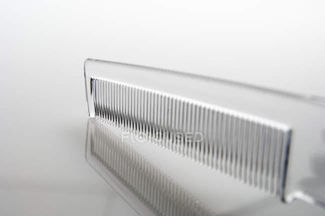 Primer plano del peine plástico transparente sobre fondo gris - foto de stock