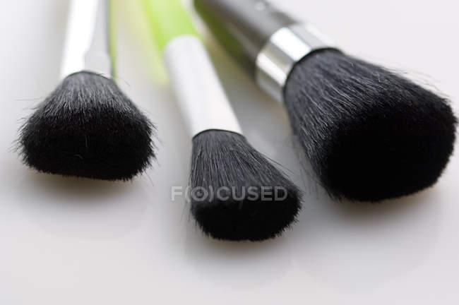 Close-up de pincéis de maquiagem na superfície branca — Fotografia de Stock