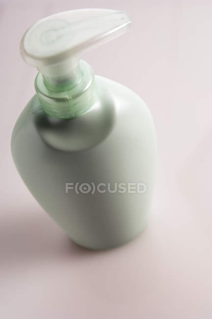 Close-up of mint colored soap dispenser on pink background — Stock Photo