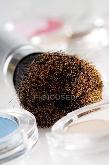 Close-up of Eye-shadow boxes and make-up brush on white background — Stock Photo